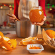 Young housewife making orange jam in christmas decorated kitchen — Stock Photo