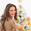 Portrait of smiling young woman decorating christmas tree — Stock Photo