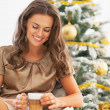 Young woman with latte macchiato in front of christmas tree — Stock Photo