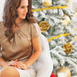 Woman sitting near christmas tree and looking  on copy space — Stock Photo