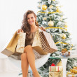 Happy young woman with shopping bags near christmas tree — Stock Photo