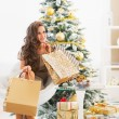Thoughtful happy young woman with shopping bags near christmas tree — Stock Photo