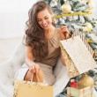 Smiling young woman with shopping bags near christmas tree — Stock Photo