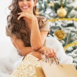 Young woman with shopping bags sitting near christmas tree — Stock Photo