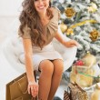 Smiling young woman among shopping bags near christmas tree — Stock Photo