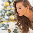 Young woman blowing out candle in front of christmas tree — Stock Photo