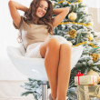 Relaxed young woman sitting near christmas tree — Stock Photo #36995683