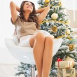 Relaxed young woman sitting in front of christmas tree — Stock Photo #36995693