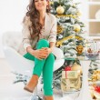 Modern young woman sitting near christmas tree — Stock Photo #36995749