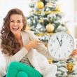 Happy young woman pointing on clock in front of christmas tree — Stock Photo #36996075