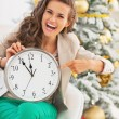 Smiling young woman pointing on clock in front of christmas tree — Stock Photo