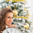 Happy young woman with clock in front of christmas tree — Stock Photo