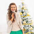 Happy young woman singing in front of christmas tree — Stock Photo #36996173