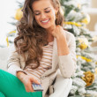 Happy young woman using tv remote control near christmas tree — Stock Photo