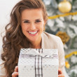 Woman holding christmas present box in front of christmas tree — Stock Photo