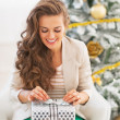 Woman opening christmas present box in front of christmas tree — Stock Photo