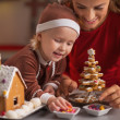 Happy mother and baby making christmas cookie house in kitchen — Stock Photo