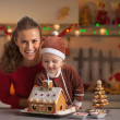 Mother and baby decorating christmas cookie house in kitchen — Stock Photo