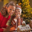 Mother and baby eating cookie in christmas decorated kitchen — Stock Photo