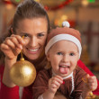 Happy mother and baby showing christmas ball — Stock Photo
