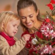 Baby helping mother decorate christmas tree — Stock Photo