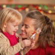 Portrait of happy mother and baby with chocolate santa — Stock Photo