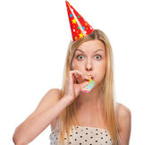 Portrait of teenage girl in cap blowing in party horn blower — Stock Photo