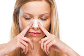 Portrait of teenage girl applying clear-up strips on nose — Stock Photo