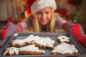 Closeup on smiling teenage girl in santa hat pulling out pan of fresh cookies — Stockfoto