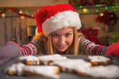 Smiling teenage girl in santa hat pulling out pan of fresh cookies — Stock Photo