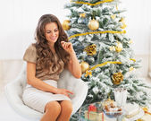 Thoughtful young woman sitting near christmas tree — Stock Photo