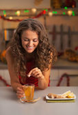 Happy young woman putting brown sugar cube into ginger tea — Stock Photo