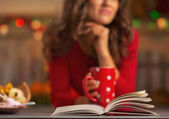 Book and thoughtful young woman with cup of hot chocolate — Stockfoto