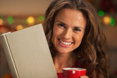 Portrait of happy young woman with book cup of hot chocolate — Stockfoto