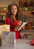 幸福的年轻女人购物袋礼品列表中检查 — 图库照片