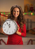 Portrait of smiling young woman holding clock in christmas decorated kitchen — Stock Photo