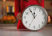Closeup on woman showing clock in christmas decorated kitchen — Stock Photo