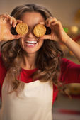 Happy young housewife holding christmas cookie in front of eyes — Photo