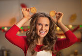 Happy young housewife making ears using christmas cookies — Stok fotoğraf