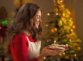 Happy young housewife showing christmas cookies — Stock Photo