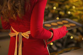 Closeup on young housewife holding pan of fresh cookies — Stockfoto