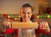 Smiling young housewife showing rolling pin — Stock Photo