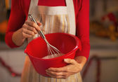 Closeup on young housewife using dough whisk — Stock Photo