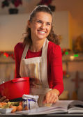 Happy young housewife preparing christmas dinner in kitchen — Stock Photo
