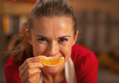 Happy young housewife holding orange in front of face — Stock Photo