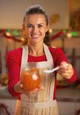 Happy young housewife giving spoon of orange jam — Stock Photo