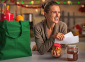 Smiling young housewife with receipts from christmas purchases — Stock Photo