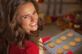 Portrait of happy young housewife holding pan with christmas cookies — Stock Photo