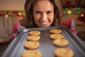 Happy young housewife showing pan with christmas cookies — Stock Photo