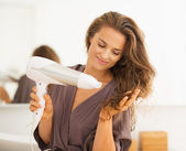 Happy young woman blow drying hair in bathroom — Photo